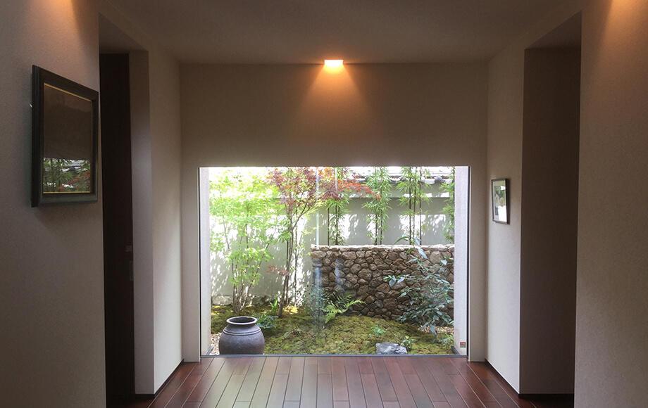 玄関ホールからの眺め。モミジのしなやかさと石積塀の硬質な造形が美しい景を創出