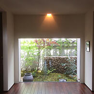 玄関ホールからの眺め。モミジのしなやかさと石積塀の硬質な造形が美しい景を創出 サムネイル
