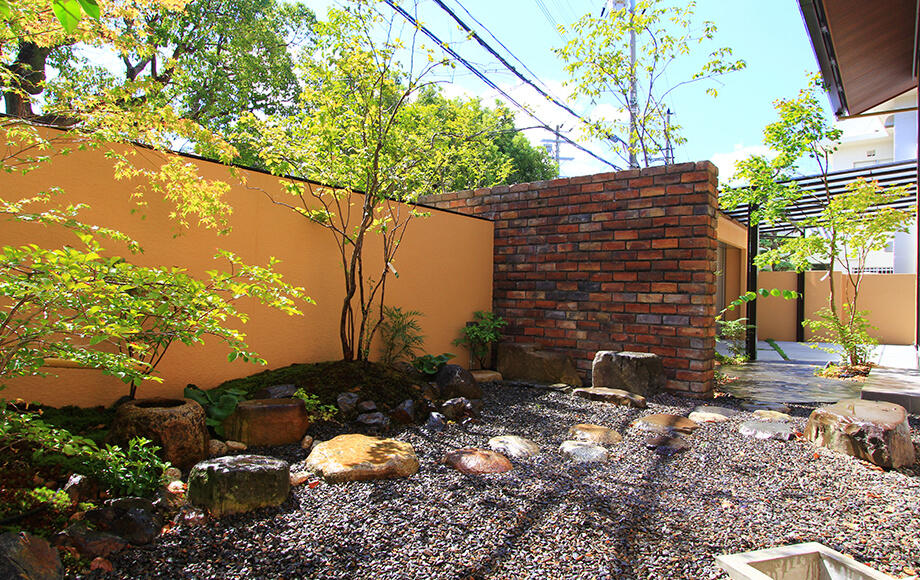 固定概念を拭い去り、あえて和庭とアプローチをレンガの壁で仕切っている