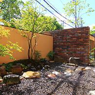 固定概念を拭い去り、あえて和庭とアプローチをレンガの壁で仕切っている サムネイル